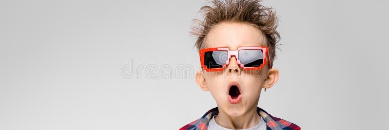 Un muchacho hermoso en una camisa de tela escocesa, camisa gris y vaqueros se coloca en un fondo gris Gafas de sol que llevan de  imágenes de archivo libres de regalías