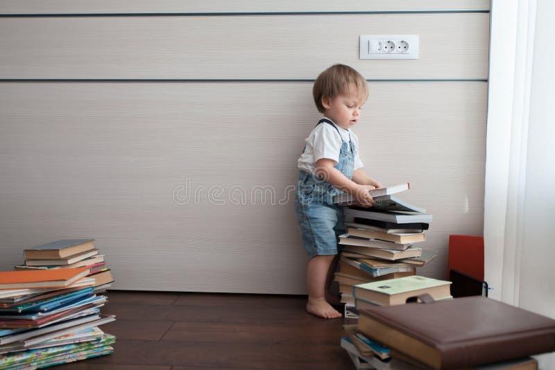 Un muchacho hermoso toma un libro y una pila grande fotografía de archivo