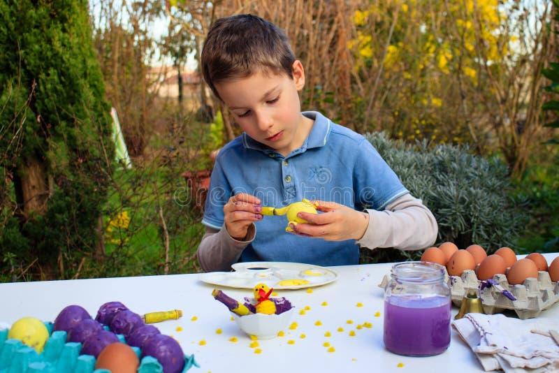 Un muchacho joven que pinta los huevos de Pascua al aire libre en Francia Actividad creativa de los niños de Pascua imagen de archivo libre de regalías