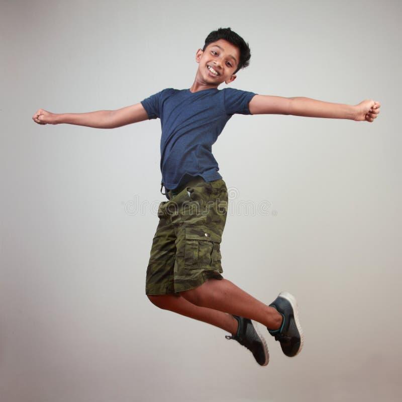 Un muchacho joven que salta en el entusiasmo imagen de archivo libre de regalías