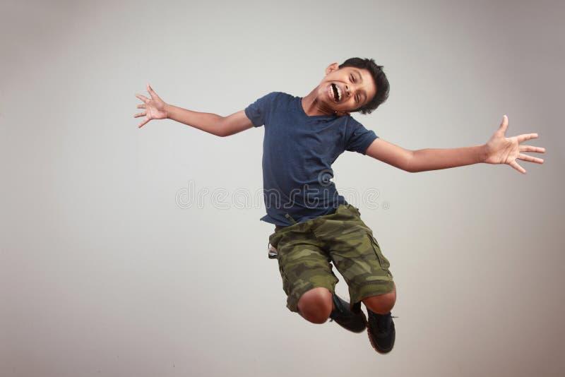 Un muchacho joven que salta en el entusiasmo fotos de archivo libres de regalías