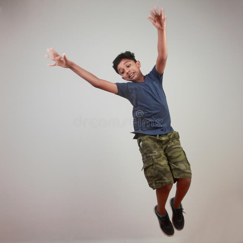 Un muchacho joven que salta en el entusiasmo fotografía de archivo
