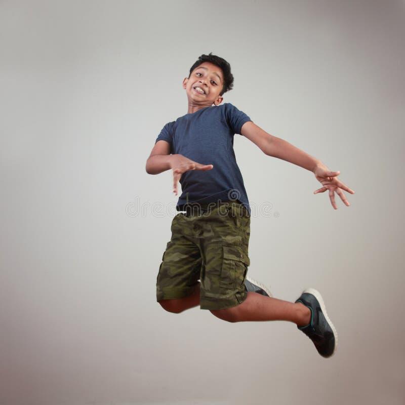 Un muchacho joven que salta en el entusiasmo imágenes de archivo libres de regalías