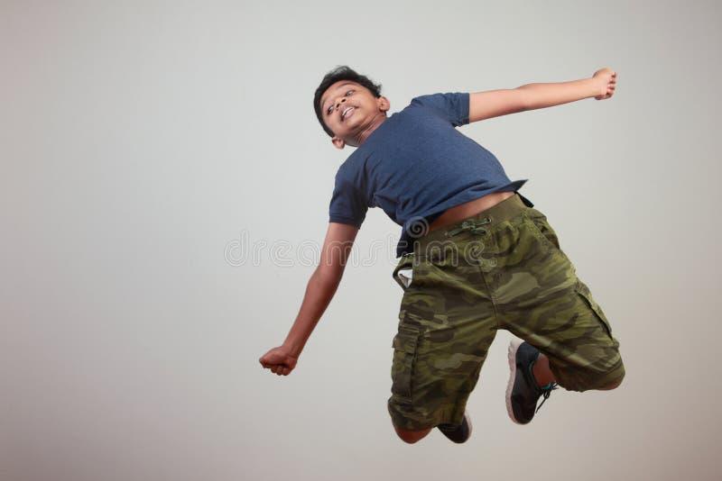 Un muchacho joven que salta en el entusiasmo fotografía de archivo libre de regalías