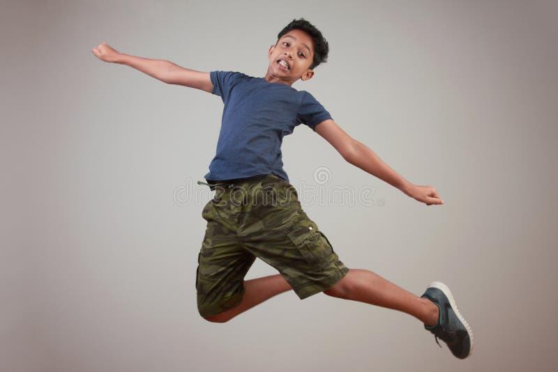 Un muchacho joven que salta en el entusiasmo imagenes de archivo