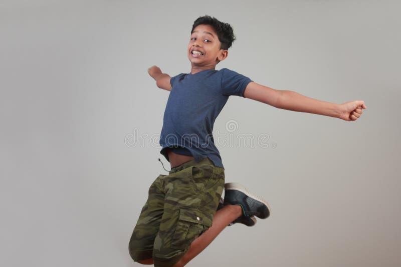 Un muchacho joven que salta en el entusiasmo imagen de archivo