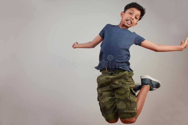 Un muchacho joven que salta en el entusiasmo foto de archivo
