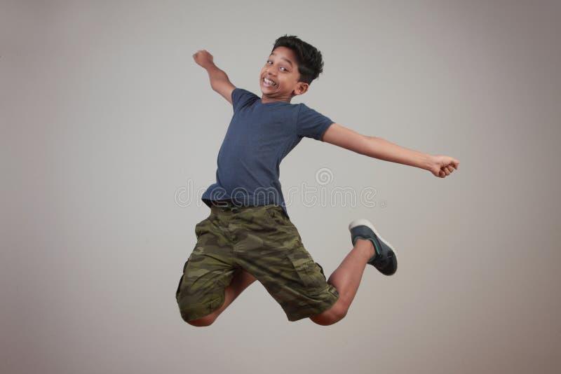 Un muchacho joven que salta en el entusiasmo fotos de archivo