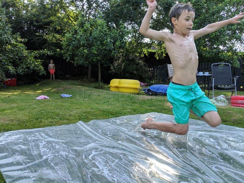 Un muchacho joven que salta sobre un resbalón y una diapositiva foto de archivo