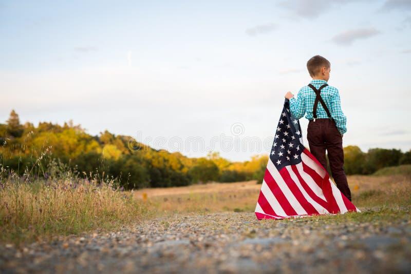 Un muchacho joven que sostiene una bandera americana grande, Día de la Independencia imagen de archivo libre de regalías