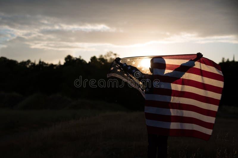 Un muchacho joven que sostiene una bandera americana grande, Día de la Independencia imagenes de archivo