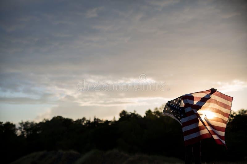 Un muchacho joven que sostiene una bandera americana grande, Día de la Independencia fotos de archivo