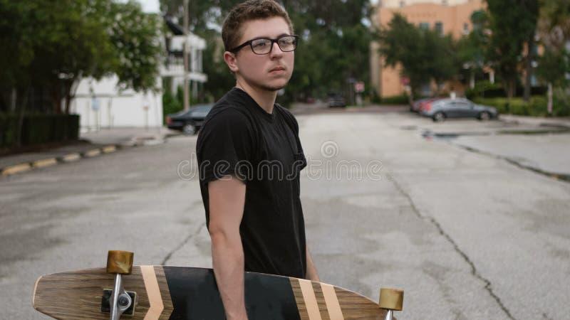 Un muchacho joven sostiene su monopatín imagenes de archivo