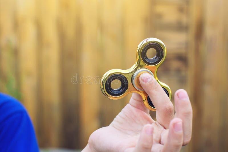 Un muchacho juega con el hilandero que lo tuerce en su mano encendido al aire libre Tendencias en los juguetes antiesfuerzos de l imagen de archivo