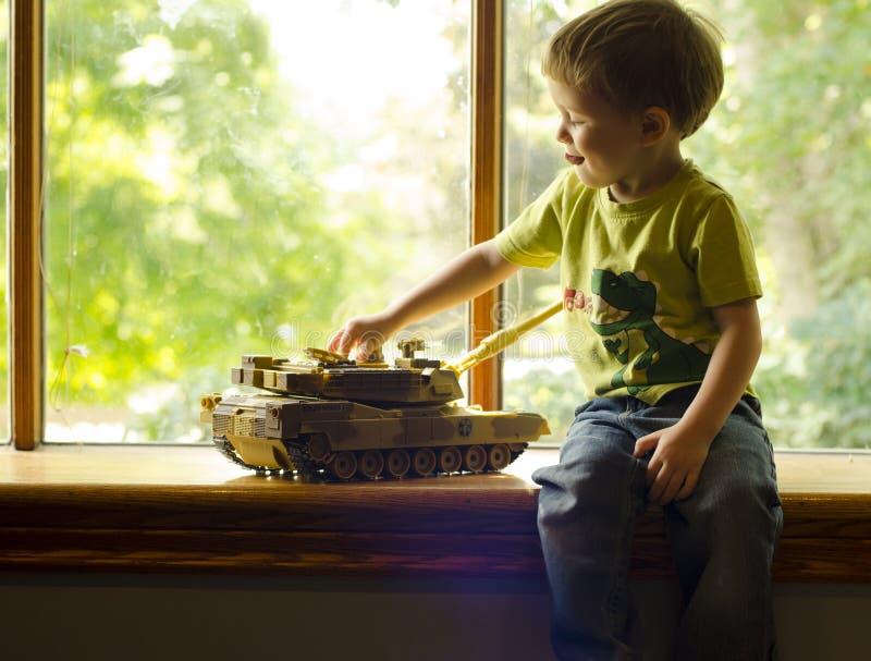 Un muchacho juega con el tanque del juguete imagenes de archivo