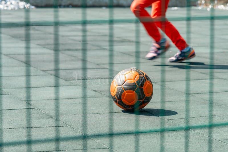 Un muchacho juega a fútbol solamente y golpea la bola con el pie, un balón de fútbol en un estadio del juego de niños fotografía de archivo