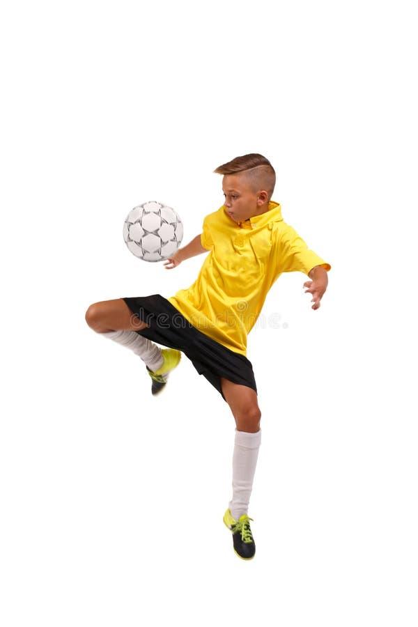 Un muchacho juguetón que golpea un balón de fútbol con el pie Un niño en un uniforme del fútbol aislado en un fondo blanco Concep fotos de archivo