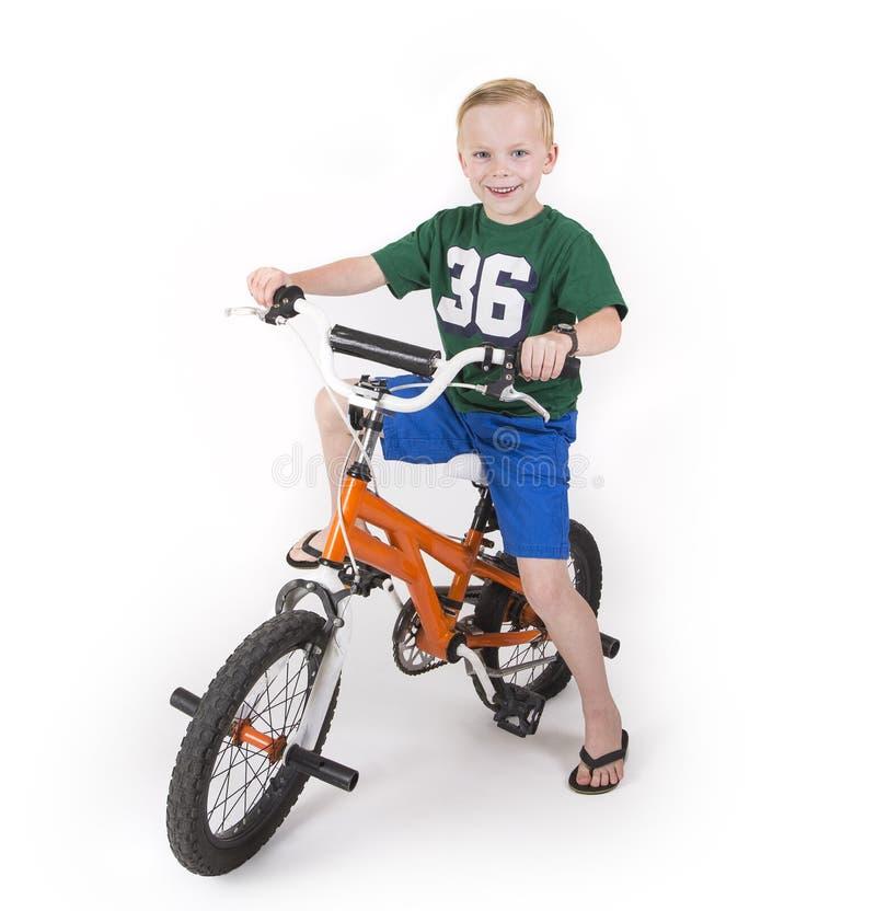 Un muchacho lindo que monta su bici aislada en el fondo blanco fotografía de archivo
