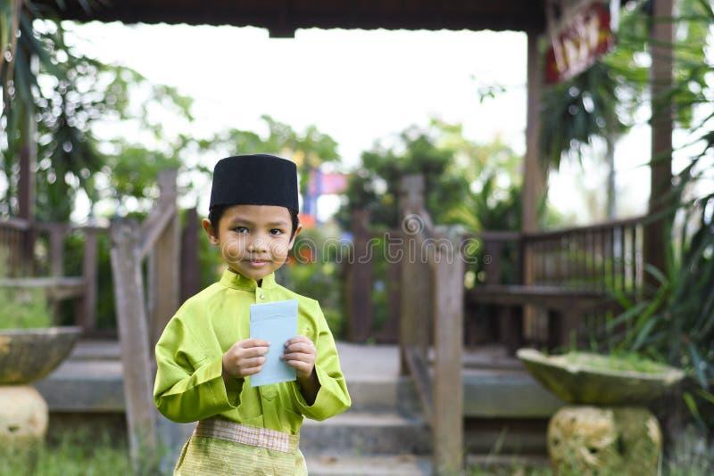 Un muchacho malayo en el paño tradicional malayo que muestra su reacción feliz después de bolsillo recibido del dinero durante el fotografía de archivo libre de regalías