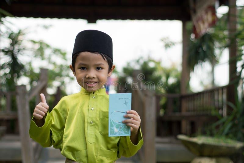 Un muchacho malayo en el paño tradicional malayo que muestra su reacción feliz después de bolsillo recibido del dinero durante el imágenes de archivo libres de regalías