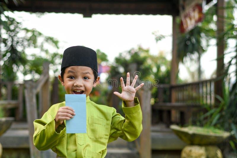 Un muchacho malayo en el paño tradicional malayo que muestra su reacción feliz después de bolsillo recibido del dinero durante el imagen de archivo libre de regalías