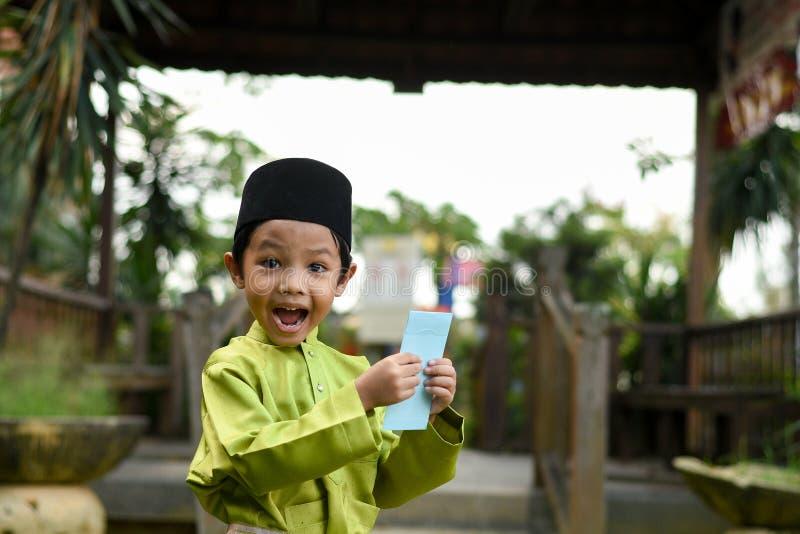 Un muchacho malayo en el paño tradicional malayo que muestra su reacción feliz después de bolsillo recibido del dinero durante el foto de archivo libre de regalías