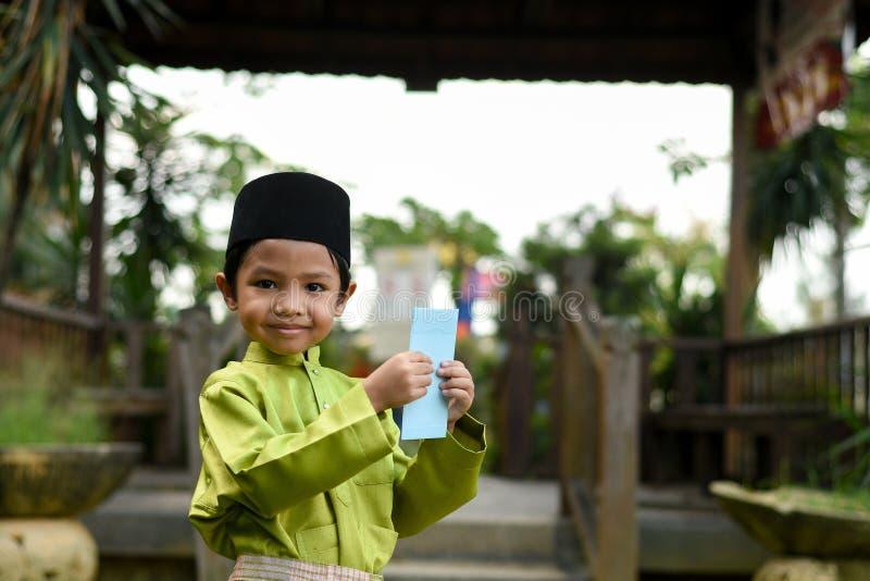 Un muchacho malayo en el paño tradicional malayo que muestra su reacción feliz después de bolsillo recibido del dinero durante el imagenes de archivo