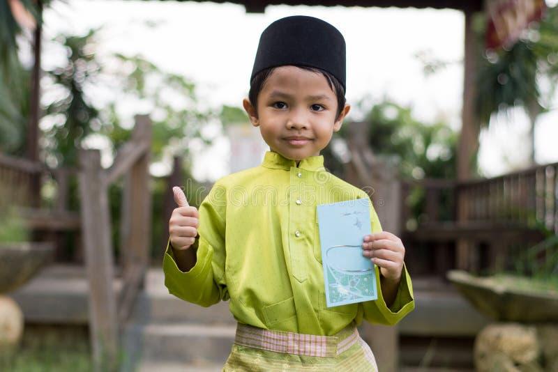 Un muchacho malayo en el paño tradicional malayo que muestra su reacción feliz después de bolsillo recibido del dinero durante el imagen de archivo