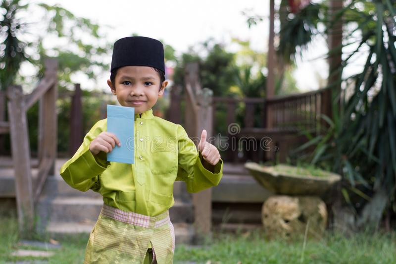 Un muchacho malayo en el paño tradicional malayo que muestra su reacción feliz después de bolsillo recibido del dinero durante el foto de archivo