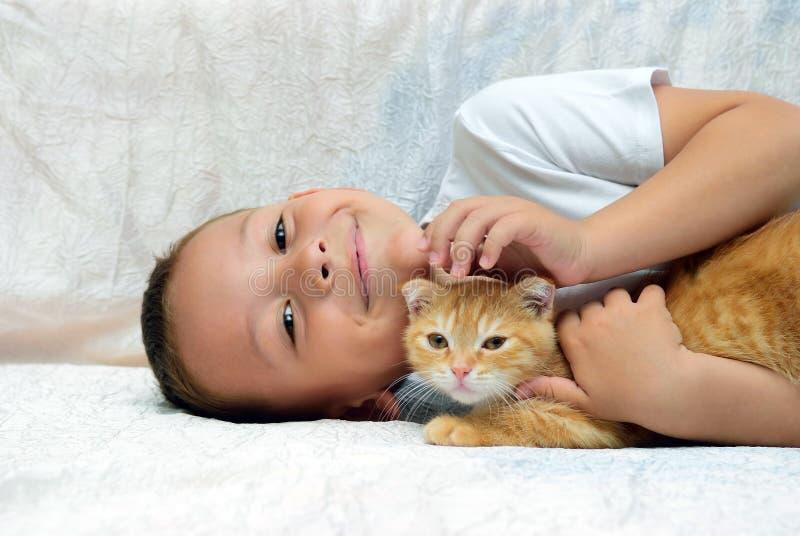 Un muchacho miente y los movimientos del gatito rojo fotografía de archivo