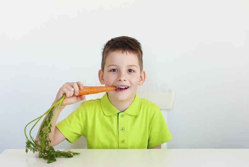 Un muchacho moreno joven que come la zanahoria imagenes de archivo