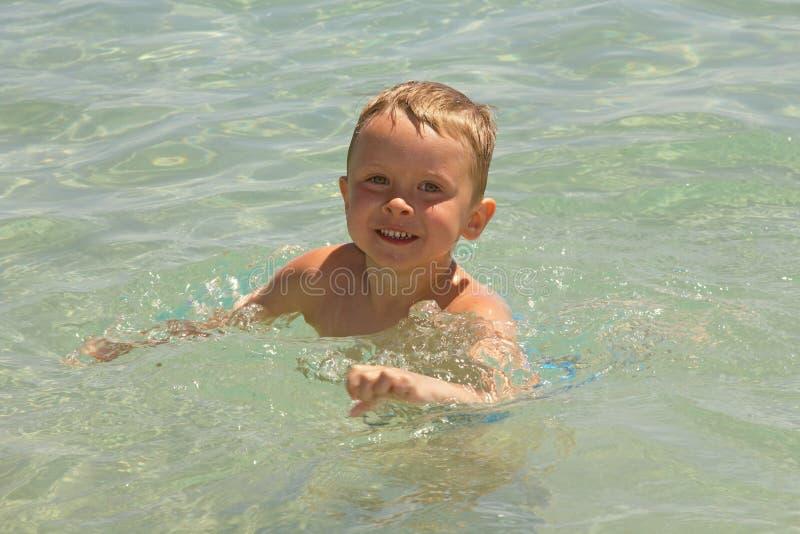 Un muchacho, nadando en un mar imagen de archivo