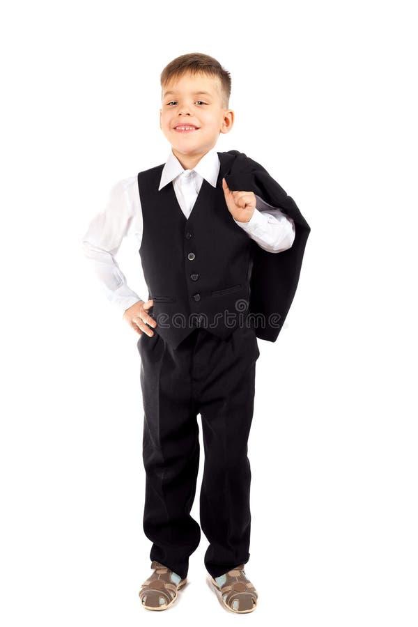 Un muchacho preescolar en una camisa blanca, un chaleco negro y pantalones foto de archivo