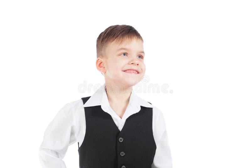 Un muchacho preescolar en una camisa blanca y un chaleco negro sonríe de par en par foto de archivo