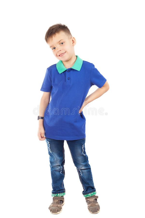 Un muchacho preescolar en una camiseta azul y vaqueros sonríe juguetónamente imagen de archivo libre de regalías