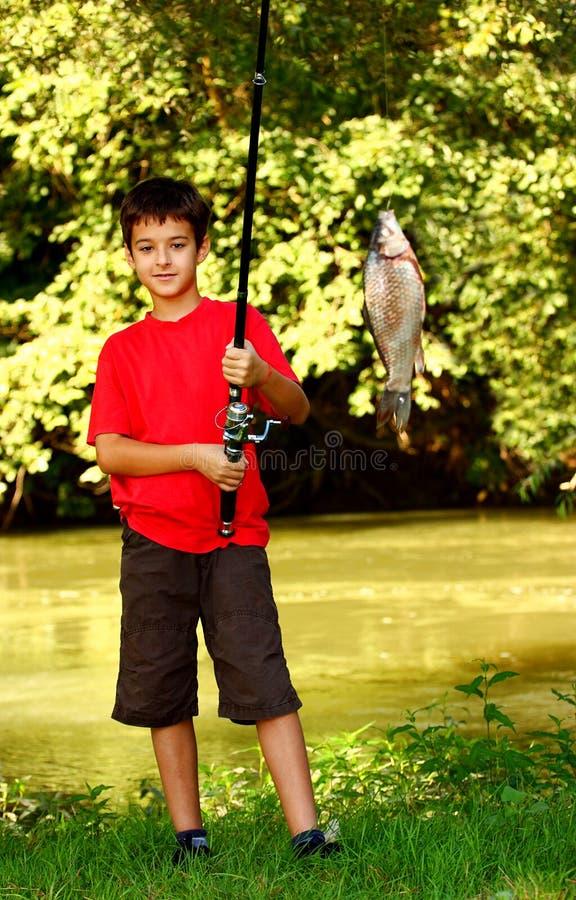 Un muchacho que coge un pescado fotografía de archivo