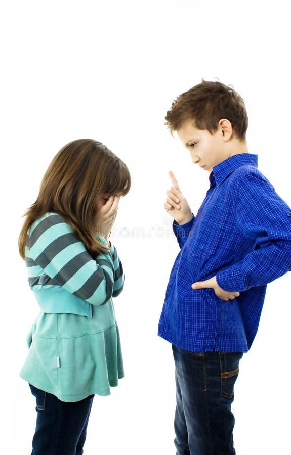 Un muchacho que señala los dedos en muchacha. La muchacha está gritando fotos de archivo