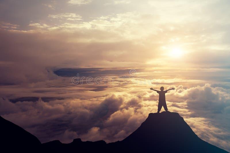 Un muchacho que se coloca en el top de la montaña sobre las nubes succ fotografía de archivo