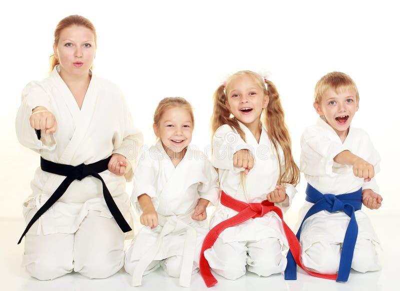 Un muchacho que se sentaba con su hermana y la mamá con su hija en un karate ritual de la actitud y batieron su puño foto de archivo
