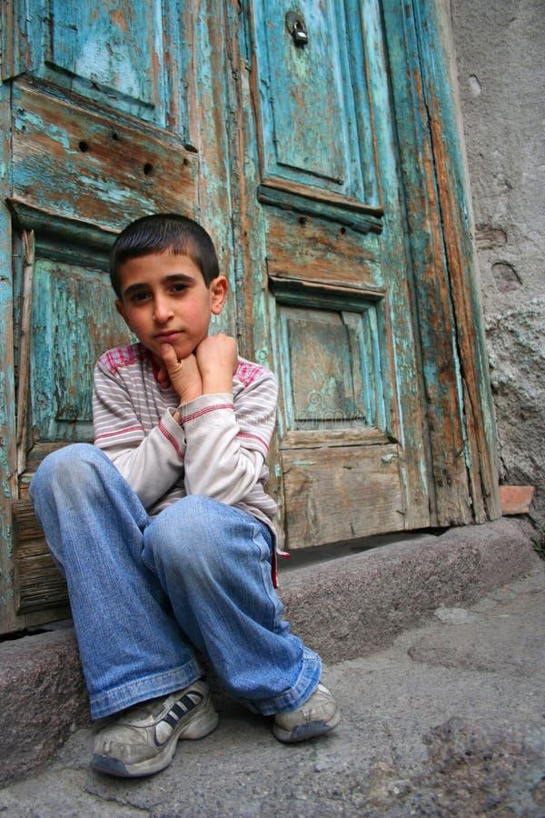 Un muchacho que se sienta en el umbral fotografía de archivo