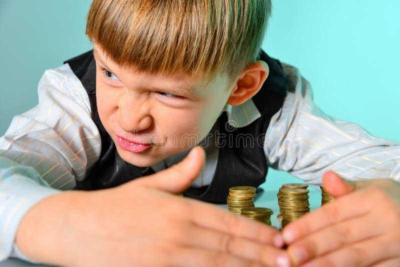 Un muchacho rico codicioso y codicioso con el dinero mira alrededor, ocultando monedas de ladrones y de enemigos imagenes de archivo