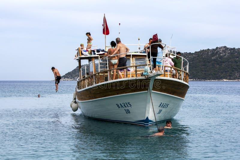 Un muchacho salta de un barco turístico de la travesía en el mar Mediterráneo cerca de la isla de Kekova en Turquía foto de archivo