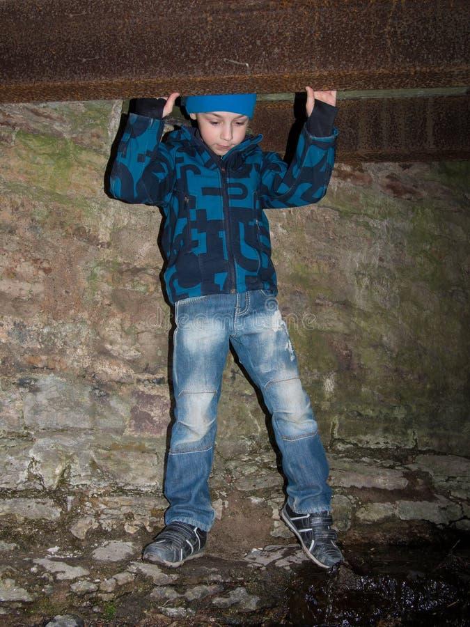 Un muchacho se coloca en una cueva imagenes de archivo