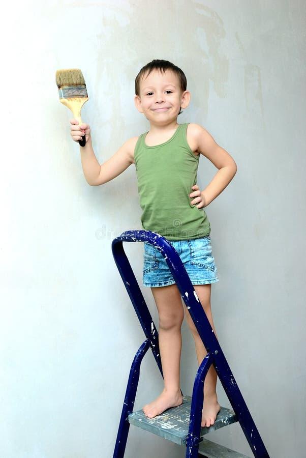 Un muchacho se coloca en una escalera con un cepillo en su mano fotografía de archivo