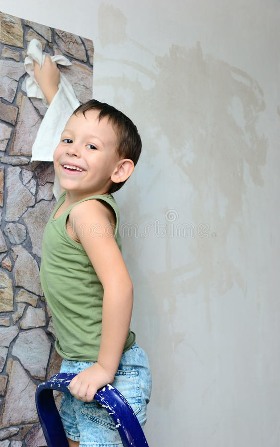 Un muchacho se coloca en una escalera y pega el papel pintado fotos de archivo libres de regalías