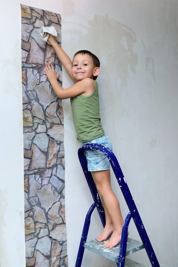 Un muchacho se coloca en una escalera y pega el papel pintado imagenes de archivo