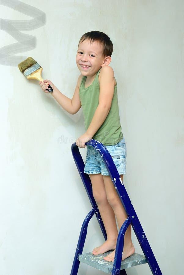 Un muchacho se coloca en una escalera y pinta la pared foto de archivo libre de regalías
