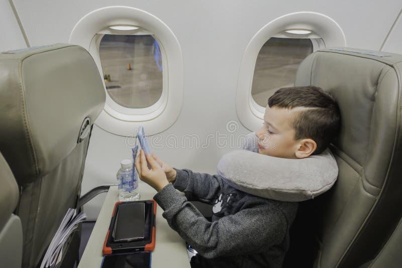 Un muchacho se está sentando en un avión cerca de la porta con la almohada del viaje, jugando en un artilugio y para un despegue  fotos de archivo libres de regalías