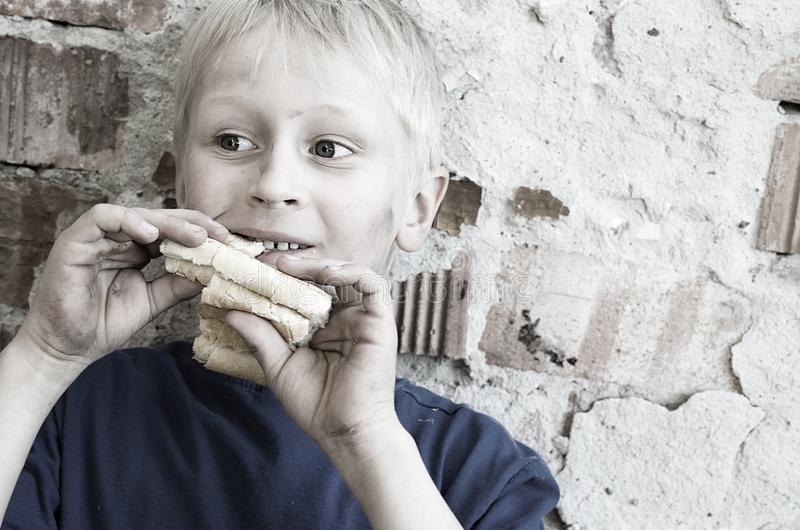 Un muchacho sucio hambriento codicioso come una corteza del pan contra la pared tono foto de archivo libre de regalías