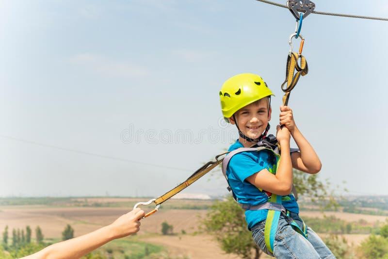 Un muchacho vestido en un casco y un seguro protectores, va abajo de la cuerda, desciende sosteniendo un cable protector fotografía de archivo